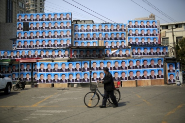 A man with a bicycle walks past a building covered in posters of Chinese President Xi Jinping in Shanghai, China, March 26, 2016. REUTERS/Aly Song/File Photo - S1AEUJNFZLAA
